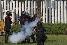 Полицейские запускают в протестующих баллон со слезоточивым газом во время стычек у стадиона в Бангкоке 26 декабря 2013 года. Тайская полиция впервые за две недели применила в четверг слезоточивый газ и резиновые пули против демонстрантов в Бангкоке, после того как толпа попыталась помешать подготовке досрочных выборов, намеченных на февраль. REUTERS/Chaiwat Subprasom