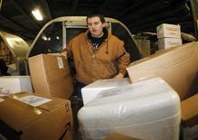 Работник UPS загружает коробки в терминале UPS в аэропорту Луисвилля, штат Кентукки, 17 декабря 2013 года. UPS не справляется с огромными объемами рождественских посылок и доставляет их с задержкой, сообщила в среду транспортно-логистическая компания. REUTERS/John Sommers II