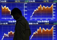 Мужчина проходит мимо экрана с графиками динамики валютных курсов в Токио 16 декабря 2013 года. Азиатские фондовые рынки завершили торги четверга разнонаправленно на фоне слабой активности инвесторов после Рождества. REUTERS/Toru Hanai