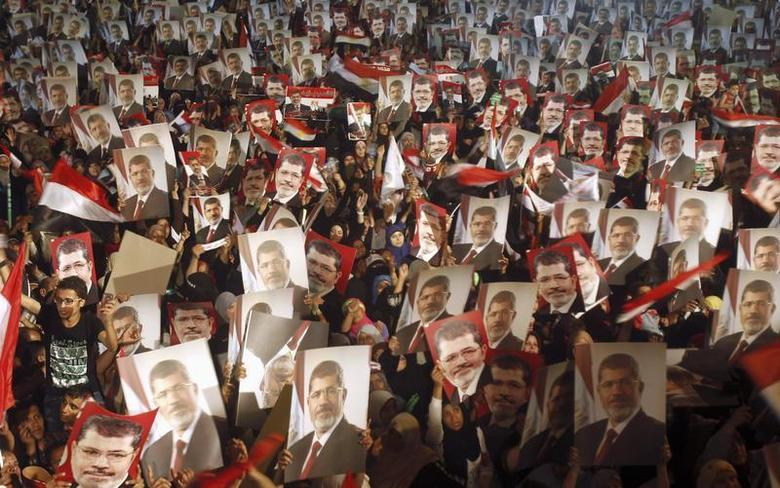 Members of the Muslim Brotherhood and supporters of Egypt's President Mohamed Mursi hold pictures of him as they react after the Egyptian army's statement was read out on state TV, at the Raba El-Adwyia mosque square in Cairo July 3, 2013. REUTERS/Khaled Abdullah