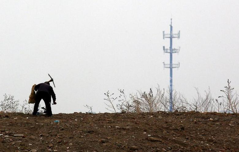 A mobile phone tower is seen behind a man carrying a pick over his shoulder as he walks past an area that will soon be a construction site on the outskirts of Beijing April 25, 2011. REUTERS/David Gray