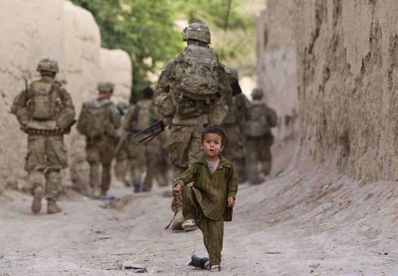 A boy plays on a street as U.S. Army soldiers of the Battle company, 1-508 Parachute Infantry battalion, 4th Brigade Combat Team, 82nd Airborne Division, patrol during a mission in Zahri district of Kandahar province, southern Afghanistan May 30, 2012. REUTERS/Shamil Zhumatov