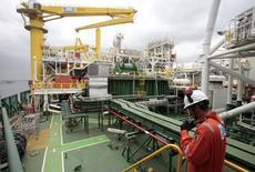 Um funcionário inspeciona a FPSO OSX-1, a primeira unidade flutuante de produção e armazenamento (FPSOs) da frota da OSX, no porto do Rio de Janeiro. A OSX Brasil, empresa de construção naval do grupo EBX, de Eike Batista, informou na noite de quarta-feira que firmou acordo com o grupo OGX, pelo qual obteve reconhecimento de valores pleiteados pela rescisão de contratos de afretamento e de operações das FPSOs OSX-1 e OSX-2 e rescisão do arrendamento da plataforma WHP 2, no valor de 1,5 bilhão de dólares. 17/11/2011 REUTERS/Sergio Moraes