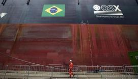 Trabajador pasa frente al FPSO OSX-1, la primera unidad flotante de producción, almacenamiento y descarga en la flota de OSX, en el puerto de Río de Janeiro, nov 17, 2011. OSX Brasil SA absorberá una participación del 7,0 por ciento de su compañía asociada Óleo e Gás Participações SA tras acordar convertir 1.500 millones de dólares de deuda en acciones, un paso clave para ayudar al atribulado productor petrolero a salir de la bancarrota. REUTERS/Sergio Moraes