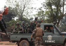 Um soldado francês olha enquanto soldados da Força Multinacional da África Central (FOMAC, na sigla em inglês) passam por Bangui. Seis soldados chadianos de uma força de paz foram mortos por milícias na capital da República Centro-Africana durante horas de combates esporádicos nesta quarta-feira, disse um porta-voz da missão de paz da União Africana. 26/12/2013 REUTERS/Andreea Campeanu