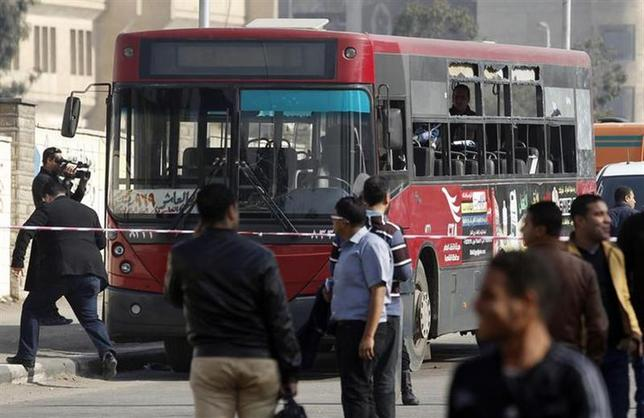 A member of the media films a damaged bus after a bomb blast near the Al-Azhar University campus in Cairo's Nasr City district December 26, 2013. REUTERS/Amr Abdallah Dalsh