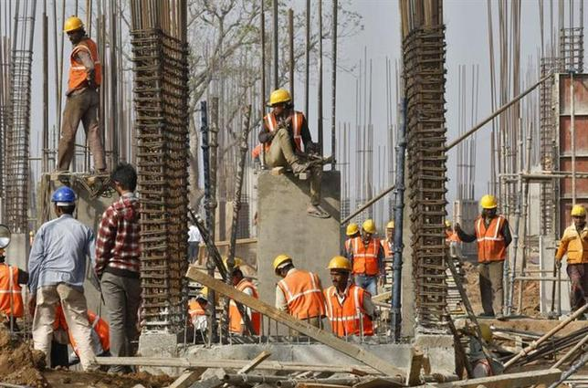 Labourers work at the construction site of an educational institute in Gujarat December 21, 2013. REUTERS/Amit Dave