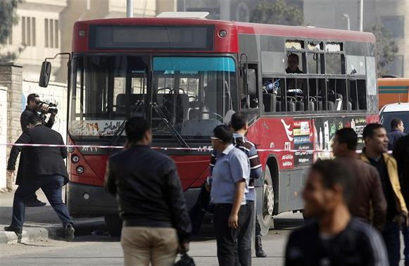 A member of the media films a damaged bus after a bomb blast near the Al-Azhar University campus in Cairo's Nasr City district December 26, 2013. REUTERS-Amr Abdallah Dalsh