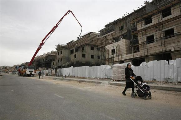 An ultra-Orthodox Jewish woman walks past a construction site in the West Bank Jewish settlement of Beitar Ilit, near Bethlehem, December 26, 2013. REUTERS/Baz Ratner