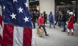 Люди на 5-й авеню в Нью-Йорке 26 декабря 2013 года. Продажи в праздничный сезон в США в этом году выросли по сравнению с прошлым годом благодаря большим скидкам и промоакциям, побуждавшим потребителей к большему числу покупок. REUTERS/Carlo Allegri