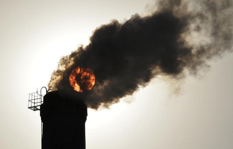 The sun is seen behind smoke billowing from a chimney of a heating plant in Taiyuan, Shanxi province December 9, 2013. REUTERS/Stringer