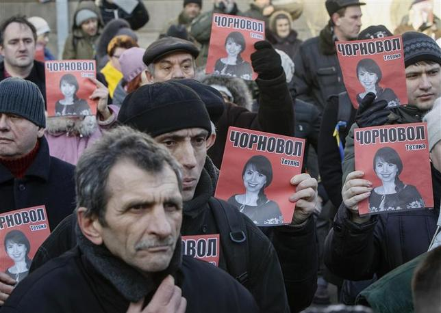 Protesters hold pictures of journalist Tetyana Chornovil, who was beaten and left in a ditch just hours after publishing an article on the assets of top government officials, during a protest rally in front of the Ukrainian Ministry of Internal Affairs in Kiev December 26, 2013. REUTERS/Gleb Garanich