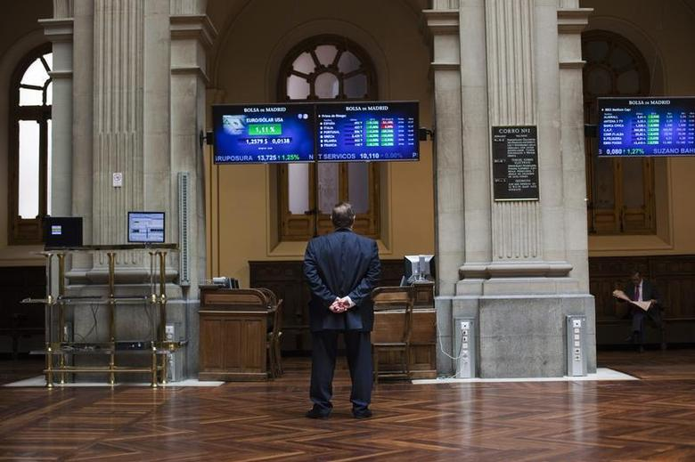A trader looks at electronic boards at Madrid's stock exchange June 29, 2012. REUTERS/Susana Vera