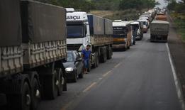 Motorista de caminhão limpa o rosto com uma taolha depois de acordar conforme espera para descarregar seu carregamento de grãos de cereal em Alto de Araguaia, perto da rodovia BR-364. A Invepar venceu nesta sexta-feira a disputa pela concessão do trecho da BR-040 (DF/GO/MG), no quinto e último leilão de rodovias federais de 2013, com oferta de deságio de 61,13 por cento sobre a tarifa de pedágio máxima permitida. 25/09/2012 REUTERS/Nacho Doce