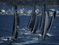 The field of yachts led by Wild Oats XI (2nd R) and Perpetual Loyal (L) sail out of Sydney Harbour at the start of the annual Sydney to Hobart yacht race, December 26, 2013. REUTERS/Jason Reed