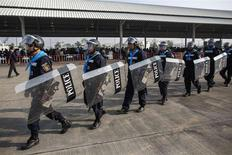 Riot policemen walk around during a registration of election candidates at a bus terminal centre near the Government complex in Bangkok December 28, 2013. REUTERS/Athit Perawongmetha