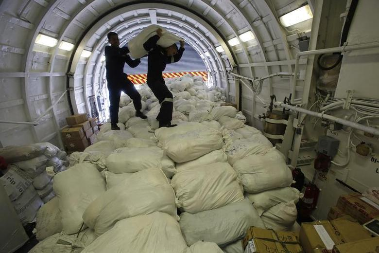 Members of the Philippine Navy carry a sack containing relief goods before transporting them to the battered town of Tacloban city, central Philippines, that was hit by super typhoon Haiyan two weeks ago, inside the latest warship BRP Ramon Alcaraz docked at a port in Manila November 22, 2013. REUTERS/Romeo Ranoco