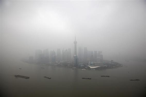 The financial district of Pudong is seen on a hazy day in Shanghai, in this file picture taken January 21, 2013. China's government is struggling to meet pollution reduction targets and has pledged to spend over 3 trillion yuan ($494 billion) to tackle the problem, creating a growing market for companies that can help boost energy efficiency and lower emissions. REUTERS-Aly Song-Files