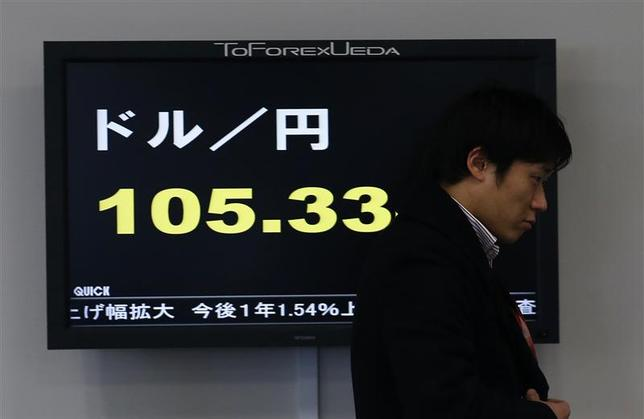 An employee of a foreign exchange company walks past a screen displaying the Japanese yen's exchange rate against the U.S. dollar in a dealing room in Tokyo December 30, 2013. REUTERS/Yuya Shino