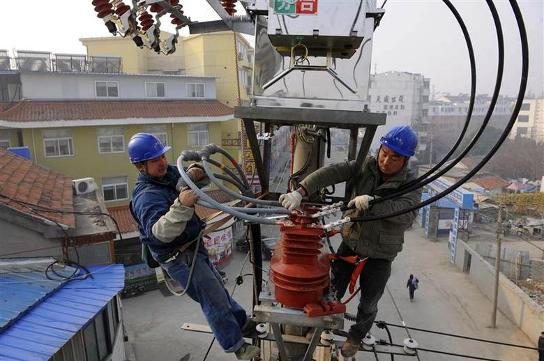 Technicians conduct maintenance work on a utility pole in Changtian, Anhui province, December 30, 2013. REUTERS/China Daily