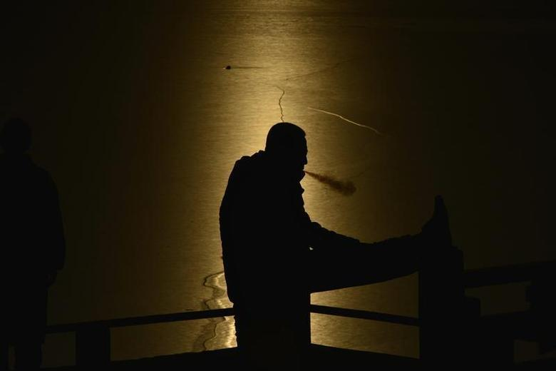 A man smokes as he stretches beside a half-frozen lake in Shenyang, Liaoning province, December 4, 2013. REUTERS/Stringer