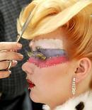 Парикмахер готовит модель к конкурсу красоты в Санкт-Петербурге 22 февраля 2007 года. Российский сектор услуг расширялся в декабре 2013 года быстрее, но ожидания компаний сектора оказались самыми пессимистичными за пять лет. REUTERS/Alexander Demianchuk