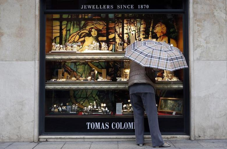 A woman looks at jewellery in a shop window in central Barcelona October 29, 2013. REUTERS/Albert Gea