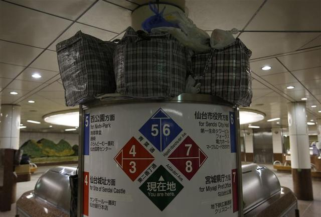 Plastic bags containing belongings of homeless men are placed on a signpost at an underground passage near Sendai Station in Sendai, northern Japan December 17, 2013. REUTERS/Issei Kato