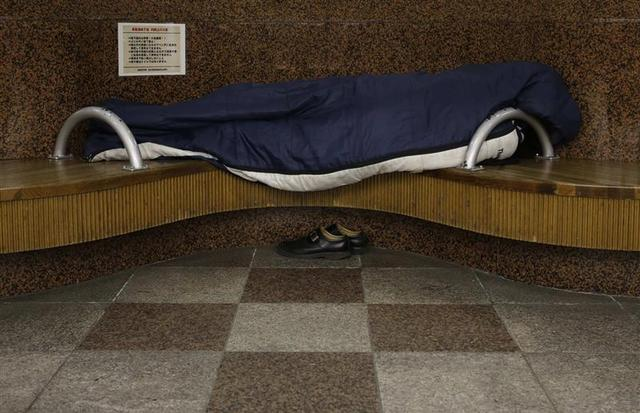 A homeless man snuggles in a sleeping bag on a bench at an underground passage near Sendai Station in Sendai, northern Japan December 17, 2013. REUTERS/Issei Kato
