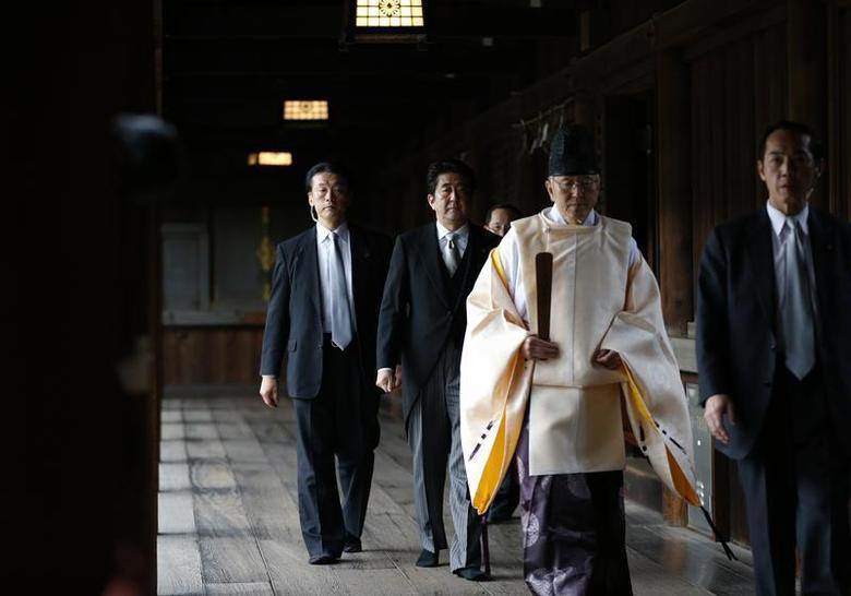 Japan's Prime Minister Shinzo Abe (2nd L) is led by a Shinto priest as he visits Yasukuni shrine in Tokyo December 26, 2013. REUTERS/Toru Hanai