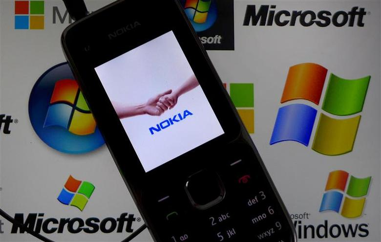 A Nokia mobile phone lies on a tablet computer showing logos of Microsoft, in this illustration picture taken in Frankfurt, November 18, 2013. REUTERS/Kai Pfaffenbach