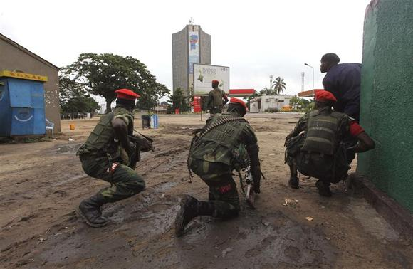 Congolese security officers position themselves as they secure the street near the state television headquarters (C) in the capital Kinshasa, December 30, 2013. REUTERS-Jean Robert N'Kengo