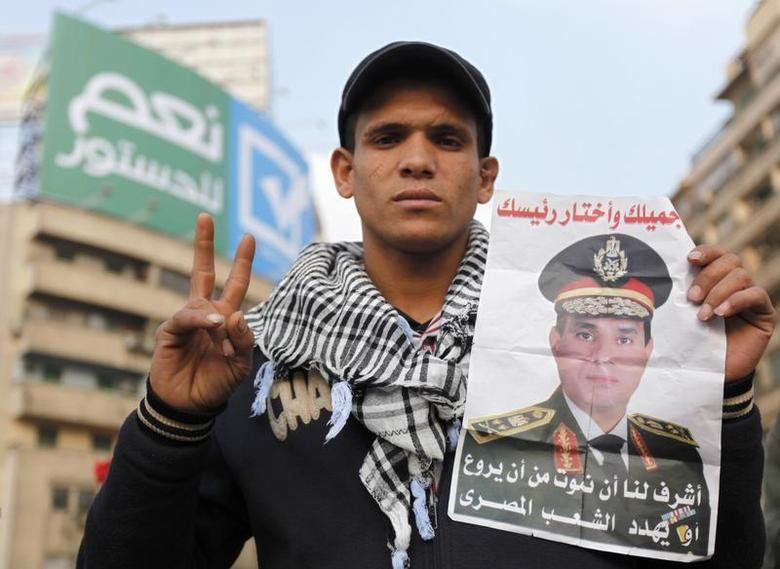 A supporter of Egypt's army chief and defense minister General Abdel Fattah al-Sisi holds a poster with Sisi's image during a protest in support of the new constitution at Tahrir Square in Cairo December 20, 2013. REUTERS/Mohamed Abd El Ghany
