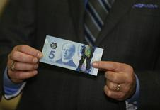 Bank of Canada Governor Stephen Poloz presents the new Canadian five dollar bill made of polymer that is entering circulation today, at the Canadian Space Agency in St. Hubert, Quebec November 7, 2013. REUTERS/Christinne Muschi