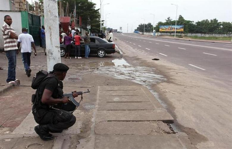 A Congolese security officer takes position to secure the street near the state television headquarters in the capital Kinshasa, December 30, 2013. REUTERS/Jean Robert N'Kengo