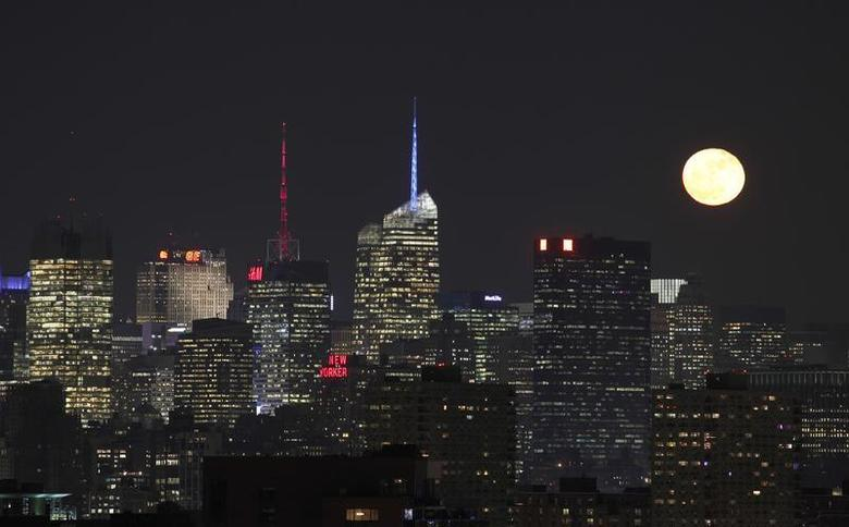 The moon rises behind the skyline of New York, as seen from Jersey City, New Jersey, December 18, 2013. REUTERS/Gary Hershorn