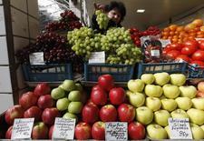 Женщина продает овощи и фрукты на рынке в Санкт-Петербурге 5 апреля 2012 года. Потребительские цены в России в 2013 году превысили ожидания чиновников и аналитиков, показав рост на 6,5 процента, а месячная инфляция по итогам декабря составила 0,5 процента к ноябрю, сообщил Росстат. REUTERS/Alexander Demianchuk