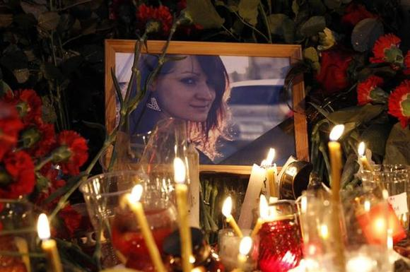 A victim's portrait is seen among flowers and candles at the site of an explosion on a trolley bus in Volgograd, December 31, 2013. REUTERS/Vasily Fedosenko