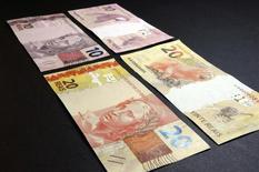 Imagen de los billetes de 20 y 10 reales brasileños. 23 de julio, 2012. La moneda brasileña cerró la última sesión de 2013 en un nivel estable, pero en el año acumuló su mayor baja ante el dólar en cinco años, en un escenario de incertidumbre global y doméstica que los analistas calculan seguirá afectando al real en 2014 y sumando volatilidad a los mercados. REUTERS/Cadu Gomes (BRASIL - NEGOCIOS)