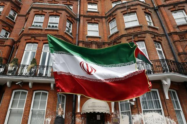 A voter holds a flag outside the Iranian consulate in central London June 14, 2013. REUTERS/Stefan Wermuth