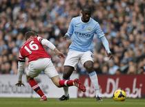 Manchester City's Yaya Toure (R) is challenged by Arsenal's Aaron Ramsey during their English Premier League soccer match at the Etihad stadium in Manchester, northern England December 14, 2013. REUTERS/Phil Noble