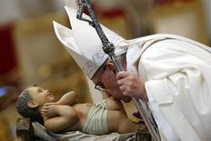 Pope Francis kisses a baby Jesus statue as he leads a mass at Saint Peter's Basilica at the Vatican January 1, 2014. REUTERS/Giampiero Sposito