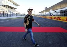 Lotus F1 Formula One driver Kimi Raikkonen of Finland walks on the track at the Suzuka circuit October 10, 2013, ahead of Sunday's Japanese F1 Grand Prix. REUTERS/Toru Hanai