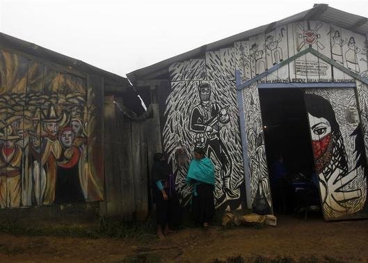 Zapatistas stand outside communal houses at the site where celebrations for the 20th anniversary of the armed indigenous insurgency will take place in Oventic December 31, 2013. REUTERS-Claudia Daut
