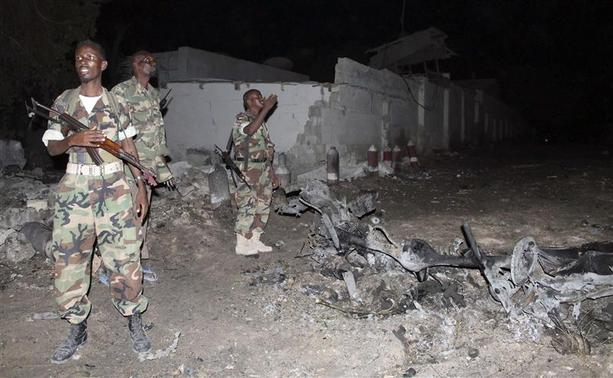 Soldiers assess the scene of an explosion outside the Jazira hotel in Mogadishu, January 1, 2014. REUTERS-Feisal Omar