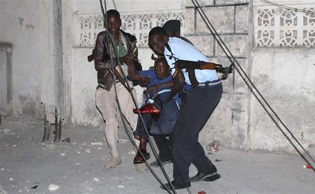 Police officers carry an injured man from the scene of a bomb attack outside the Jazira hotel in Mogadishu January 1, 2014. REUTERS-Feisal Omar