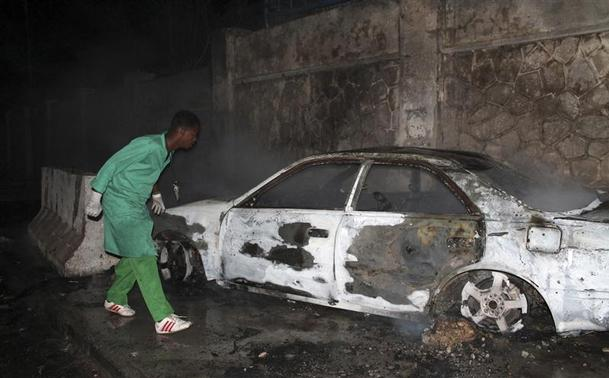 A firefighter looks at a destroyed car at the scene of an explosion outside the Jazira hotel in Mogadishu, January 1, 2014. REUTERS-Feisal Omar