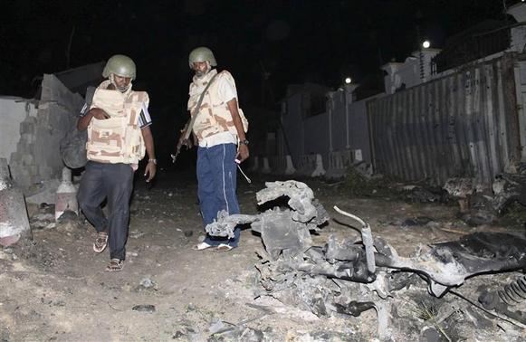 Police officers assess the scene of an explosion outside the Jazira hotel in Mogadishu, January 1, 2014. REUTERS-Feisal Omar