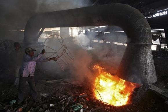 A worker throws a broken iron chair into a furnace for recycling at an iron and steel factory on the outskirts of Jammu February 1, 2013. REUTERS/Mukesh Gupta/Files