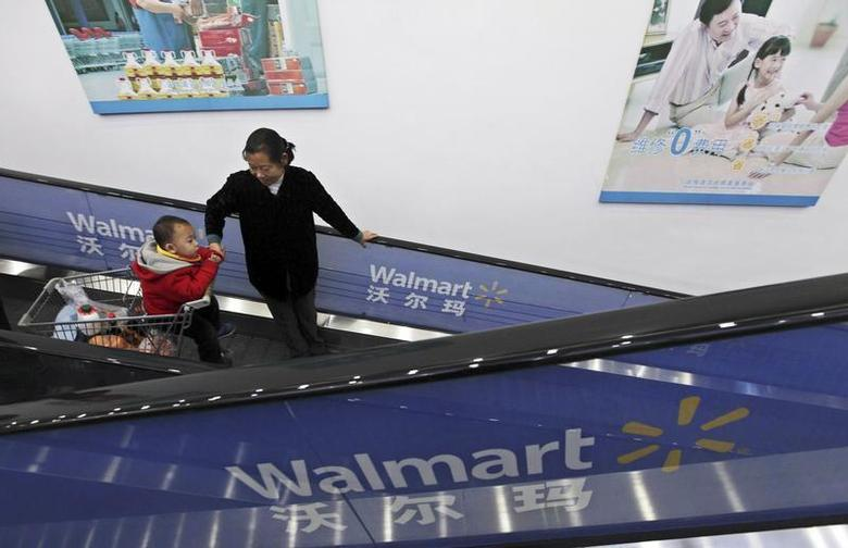 A customer looks at her child on a shopping trolley as they take an escalator at a Wal-Mart supermarket in Wuhan, Hubei province December 3, 2011. REUTERS/Stringer